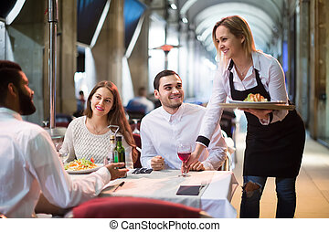 waitress bringing order at terrace table in summer day