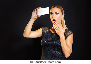 Blond fashion woman smartphone selfie in black background