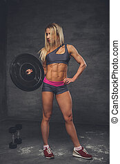 Blond female fitness model holding barbell weight