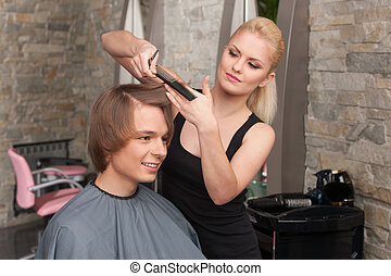 Blond female hairdresser cutting hair of man client. profile of happy man sitting in hair salon and smiling