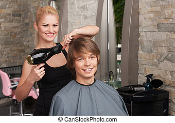 Blond female hairdresser drying hair of man client. profile of happy man sitting in hair salon and smiling