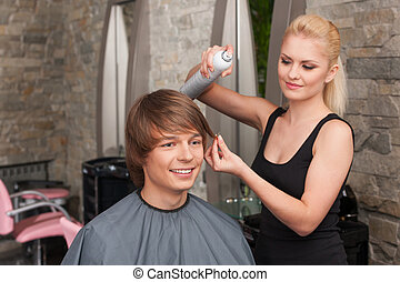 blond female hairstylist using hair spray. young attractive man sitting in hair salon and smiling