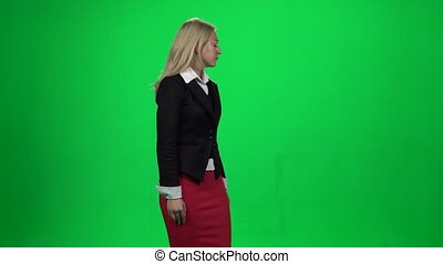 Blond female looking upset standing against green screen...