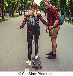 Blond female practicing on longboard with her boyfriend.