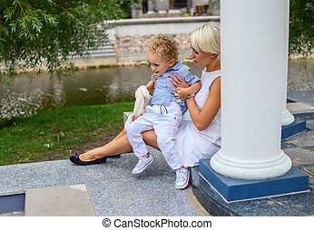Blond female relaxing with her child in a park.