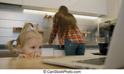 Blond female toddler watching animated videos on the kitchen while her mother washing sink.