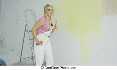 Blond female with paint roller dancing