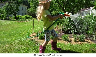 Blond gardener kid with hat holding water sprayer and spray...