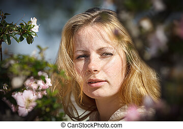 Blond girl among the flowers
