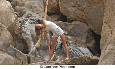 Blond Girl Does Yoga Exercises on Stone by Waterfall