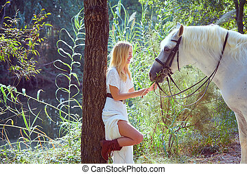 Blond girl feed grass to her white horse