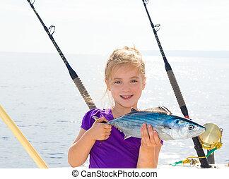 Blond girl fishing bonito Sarda tuna trolling in Mediterranean sea