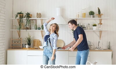 blond girl guy dance by table stove in modern kitchen