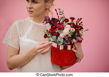 Blond girl hold bouquet in hat box