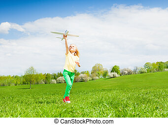 Blond girl holding airplane toy during running