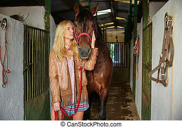 Blond girl holding horse at stable