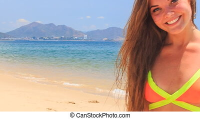 blond girl in bikini looks into camera pulls wry face on beach