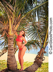 blond girl in bikini stands between palms holds branch