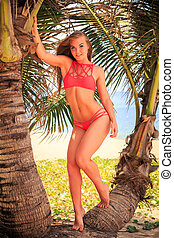blond girl in bikini stands between palms looks forward