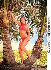 blond girl in bikini stands between palms looks forward