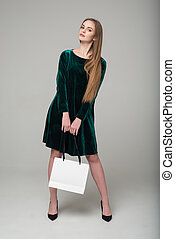 Blond girl in dark green short dress with white bag