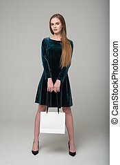 Blond girl in green short dress with white paper bag