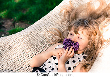 blond girl in hammock with flowers