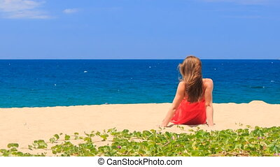 blond girl in red backside sits on beach with hands behind back
