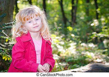blond girl in red coat in green forrest