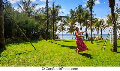 Blond Girl in Red Comes to Lawn Lies down on Grass among Palms