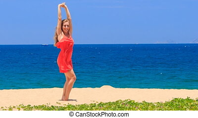 blond girl in red dances barefoot on sand beach lifts hands