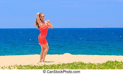 blond girl in red dances barefoot on sand beach smooths hair