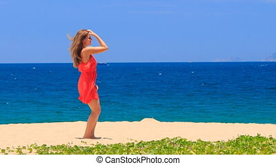 blond girl in red dances barefoot on sand beach waves hands