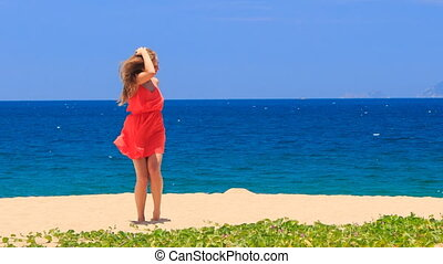 blond girl in red dances barefoot on sand holds hands on hips