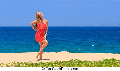 blond girl in red dances barefoot on sand touches hip dress