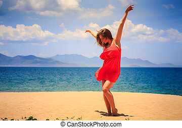 blond girl in red dances barefoot on sand with hands above