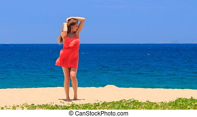 blond girl in red dances on beach smooths shaken long hair