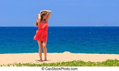 blond girl in red dances on beach smooths shaken long hair
