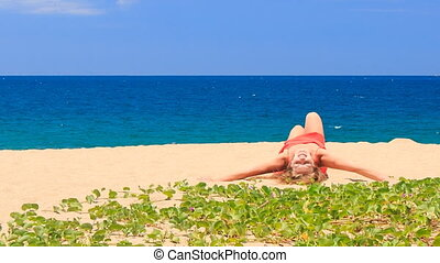 blond girl in red lies down on sand green creepers on foreground