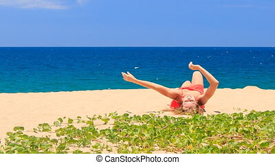 blond girl in red lies on sand waves hands near green creepers