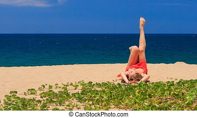 blond girl in red lies on sand waves legs near green creepers