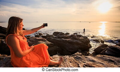 Blond Girl in Red Sits by Sea Makes Selfie at Orange Sunset