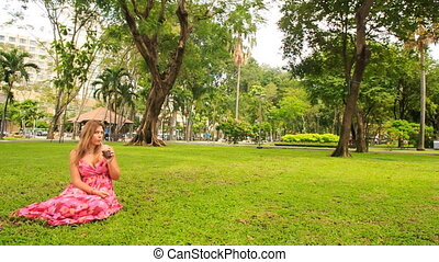 Blond Girl in Red Sits on Grass Drinks Juice with Straw