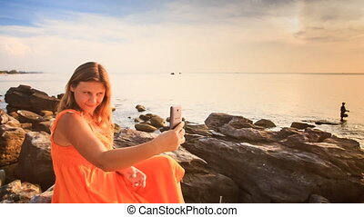 Blond Girl in Red Sits on Stones Makes Selfie by Sea at Sunset