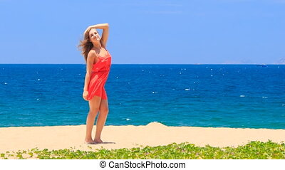 blond girl in red stands barefoot on sand beach smooths hair