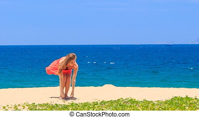blond girl in red takes off sandals on sand beach throws