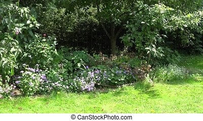 Blond girl in spotty dress mow lawn between garden trees in...