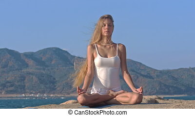 Blond Girl in Top Relaxes in Yoga Pose Lotus on Rock