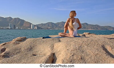 Blond Girl in Top Sits on Rock in Yoga Pose Hands behind Back