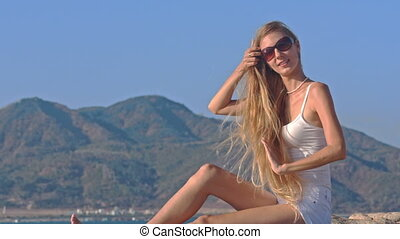 Blond Girl in Top Smoothes Hair Shaken by Wind against Sky